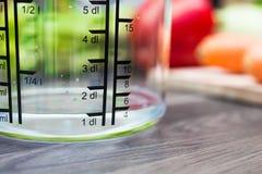 100ml/1dl di acqua in tazza di misurazione di A su un contatore di cucina con le verdure Fotografia Stock
