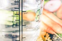 750 ml - Wasser ccm in einem Messbecher umgeben durch Nudeln, Zwiebel, Karotten und Gewürze lizenzfreies stockbild