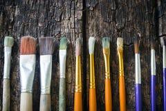 Målarfärgborstar av olika format har olika färger i rad horisontellt på ett gammalt trä Arkivbilder