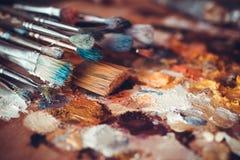 Målarpenslar closeup, palett och flerfärgade målarfärgfläckar Arkivbilder