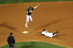 MLB - headfirst into second!. Oakland A's second baseman Mark Ellis leaps for a throw as Chicago White Sox leftfielder Scott Podsednik successfully steals second Royalty Free Stock Image