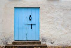 Mlecznoniebieski stary drzwi w ulicie zdjęcia stock