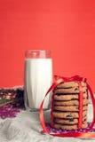 Mleko i ciastka na czerwonym tle dla Święty Mikołaj Święta dekorują odznaczenie domowych świeżych pomysłów nowy rok, Fotografia Royalty Free