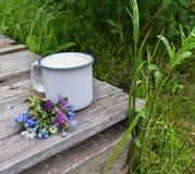Mleko i wildflowers na starym stole Fotografia Stock
