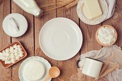 Mleko, ser i masło wokoło pustego bielu talerza na drewnianym tle, jeść zdrowo pojęcia na widok Obraz Stock