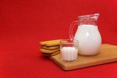 Mleko w ewer i szkle Fotografia Stock