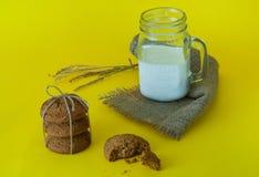 Mleko w szklanym słoju na parciaka i oatmeal ciastkach na żółtym tle, pojęcie naturalni produkty, zakończenie up, kopii przestrze Zdjęcia Royalty Free