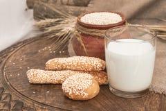Mleko w szkle, chlebowi kije, babeczki na drewnianym stole Obrazy Stock