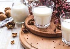 Mleko, wrzosów kwiaty i orzechy włoscy, tabela drewna Obraz Stock