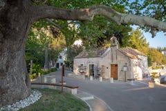 MLINI, ΚΡΟΑΤΊΑ - τον Απρίλιο του 2019: Το παλαιό sycamore δέντρο και souvernir ψωνίζει από την παλαιά παλαιά εκκλησία σε Mlini στοκ εικόνα
