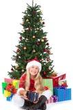 Mlle Santa avant arbre et cadeaux de Noël Photographie stock libre de droits