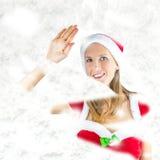 Mlle Santa jetant un coup d'oeil par la fenêtre neigeuse Images stock