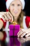 Mlle Santa ouvrant un boîte-cadeau enveloppé par rose Image libre de droits