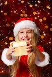 Mlle Santa secouant un cadeau Images libres de droits