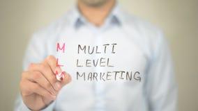 MLM, vente de niveau multi, écriture d'homme sur l'écran transparent Image libre de droits