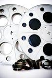 35 mm电影戏院卷与在白色展开的影片 免版税图库摄影