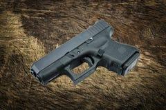 9mm automáticos pistola do revólver no fundo da árvore de casca Imagem de Stock Royalty Free