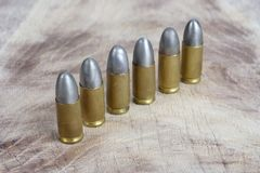 9mm caliber cartridges. On wooden background Royalty Free Stock Image