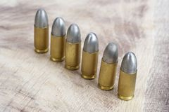 9mm caliber cartridges. On wooden background Royalty Free Stock Images