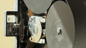 16mm film camera. Pathe 16mm film camera , the intermittent camera movement detail , film spools in the foreground stock video footage