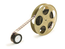 35mm Film In Reel. A 35mm film in a metallic golden reel,  over white background, with clipping paths Royalty Free Stock Image