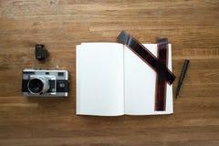 35mm Filmkamera, Notizbuch, Stift, Filmstreifen und Filmstreifen legen auf Holztisch, Ansicht von der Spitze mit CopySpace Stockbilder
