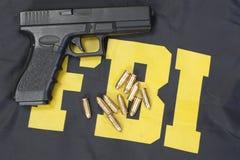 9mm handeldvapen med ammo på fbi-likformign Royaltyfri Foto