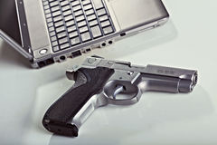 Computer Security. A 9mm handgun and  a laptop computer resting on a table. Backlit, shallow depth of field Royalty Free Stock Photo