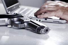 Computer Crimnal. A 9mm handgun resting on a table, and defocused in the background the hands of a mature adulat man are typing on the keyboard of a laptop Stock Image