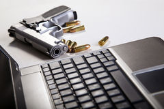 Computer Security. A 9mm handgun with scattered bullets beside it and part of a laptop computer. Backlit, shallow depth of field Stock Image