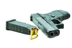 9mm Kugeln und schwarze Gewehrpistole lokalisiert auf weißem Hintergrund Stockfotografie