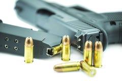 9mm Kugeln und schwarze Gewehrpistole lokalisiert auf weißem Hintergrund Lizenzfreie Stockfotografie