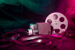 8 mm movie camera with a reel of film in green and purple smoke. Dark background stock photography
