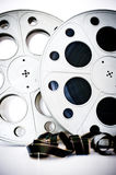 35 mm movie cinema reels with film unrolled on white Royalty Free Stock Photography