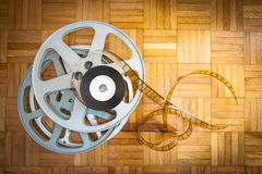 35 mm movie film reel on wooden floor. 35 mm movie filmstrip and cinema reel on wooden floor stock images