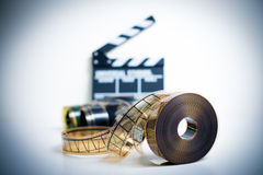 35mm movie reel with out of focus clapper in background. Color effect and vintage look royalty free stock images