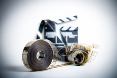 35mm movie reel with out of focus clapper in background Royalty Free Stock Photo