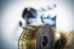 35mm movie reel with out of focus clapper in background Royalty Free Stock Photos