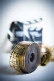 35mm movie reel with out of focus clapper in background, vertica. 35mm movie reel with out of focus clapper in background, color effect and vintage look stock photos