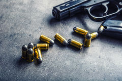 9 mm pistol gun and bullets strewn on the table Stock Photography