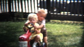 (8mm Vintage) 1954 Brother Pushing Sister Toy Tractor. Iowa, USA.
