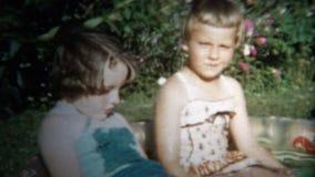 (8mm Weinlese) 1954 Mädchen, die äußere kleine Spritzen-Pools spielen Iowa, USA stock footage
