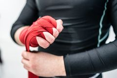 MMA boxing fighter putting hand wraps on hands royalty free stock photography