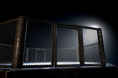 MMA Cage Night. A 3D render of an MMA fight cage arena dressed in black padding spotlit by a single light on an isolated dark background Stock Images
