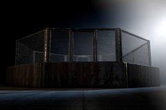 MMA Cage Night. A 3D render of an MMA fight cage arena dressed in black padding spotlit by a single light on an isolated dark background Stock Image