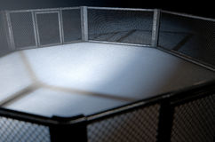 MMA Cage Night. A 3D render of an MMA fight cage arena dressed in black padding spotlit by a single light on an isolated dark background Royalty Free Stock Photography