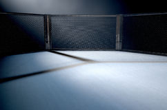MMA Cage Night. A 3D render of an MMA fight cage arena dressed in black padding spotlit by a single light on an isolated dark background Stock Photos