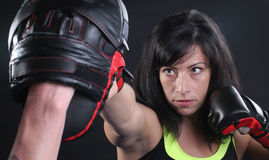 MMA Face Punch. Beautiful woman doing a straight right punch into a focus mitt royalty free stock photo