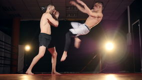 MMA fighter giving a forceful forward kick to his partner. Slow motion. stock video