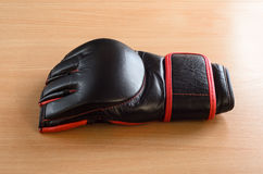 Mma gloves on wooden background. Black mma gloves on a wooden background royalty free stock photo